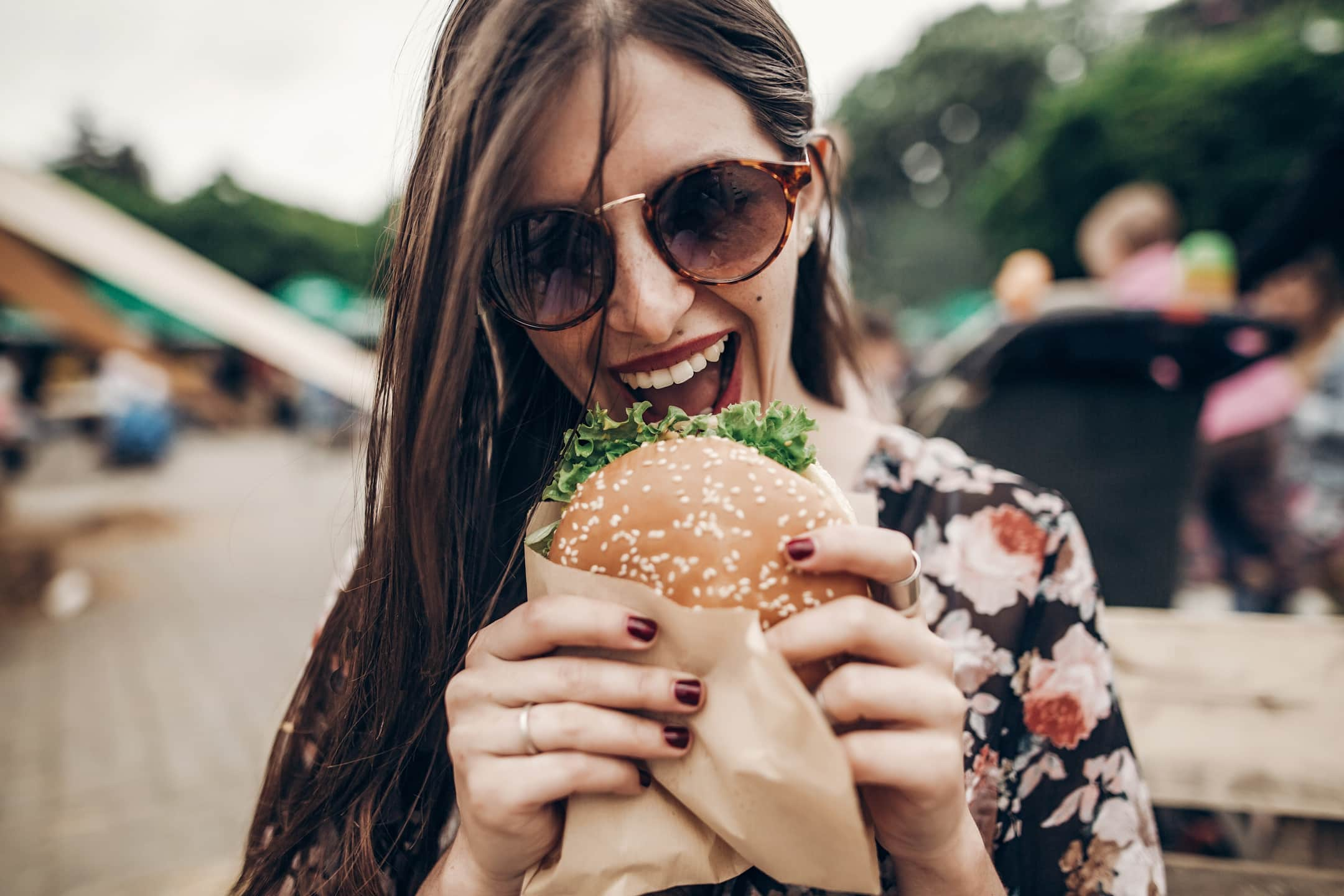 stylish hipster woman eating juicy burger. boho girl biting cheeseburger, smiling at street food festival. summertime. summer vacation travel picnic. space for text